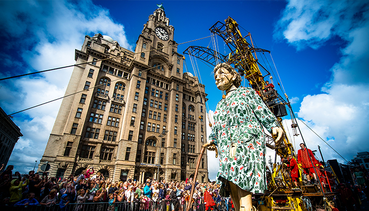 The Grandmother Giant walks passed crowds in front of the Liver Building