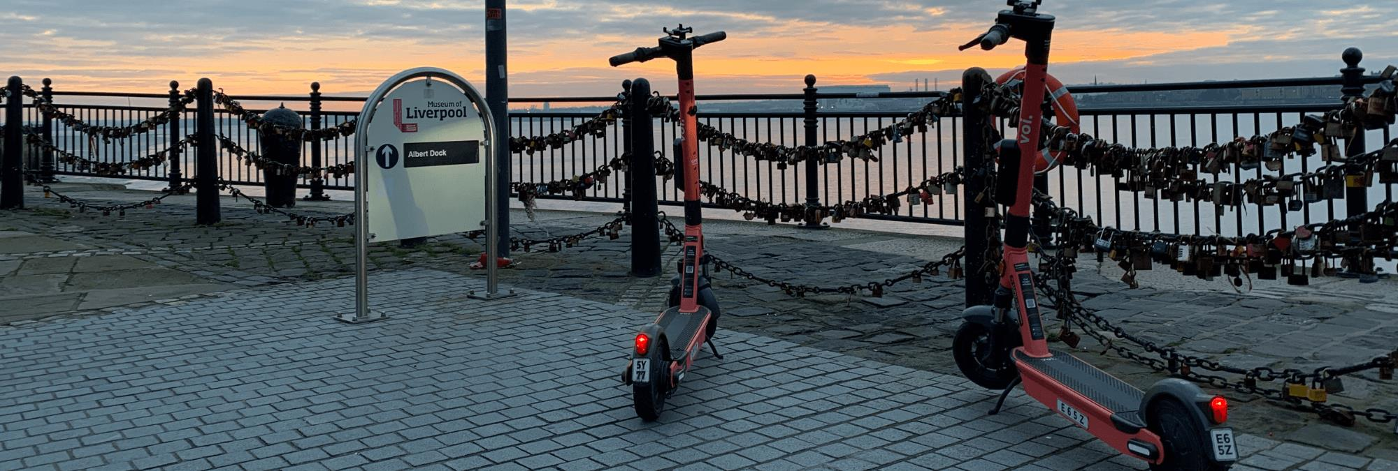 Two orange 'voi' scooters are propped on the waterfront. There is an orange sunset and love locks hang off the railings.