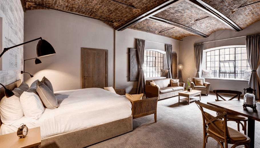 Neutral tones adorn the walls inside this hotel room which features original iron beams and exposed bricks. The room is part of a converted warehouse.