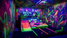 Inside the Ghetto Golf course. Neon paint and golf holes in a dark room.