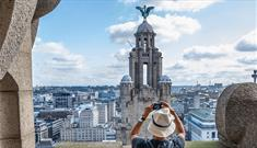 A man wearing a large hat stood inside one of the towers taking a picture of the opposite Liver Bird on a sunny day with blue skies.