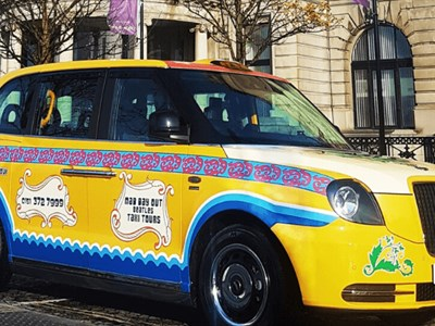 An electric Hackney Cab with psychedelic Beatles themed paint job