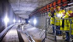 A group of people wearing yellow reflective coats and hard hats in the tunnels stood on a platform.
