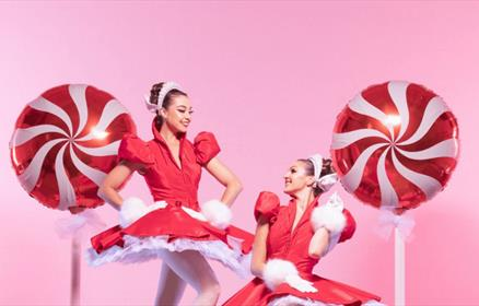 2 dancers wear festive red and white tutus surrounded by giant lollipops.