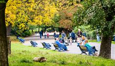 Families sit on benches within Sefton Park during Autumn time. The trees have yellow, red and green leaves.