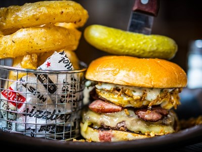 A large burger with a gherkin on the top next to a small basket of onion rings.