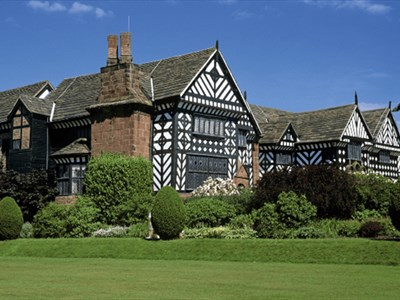 Outside of Speke Hall with green grass and trees.