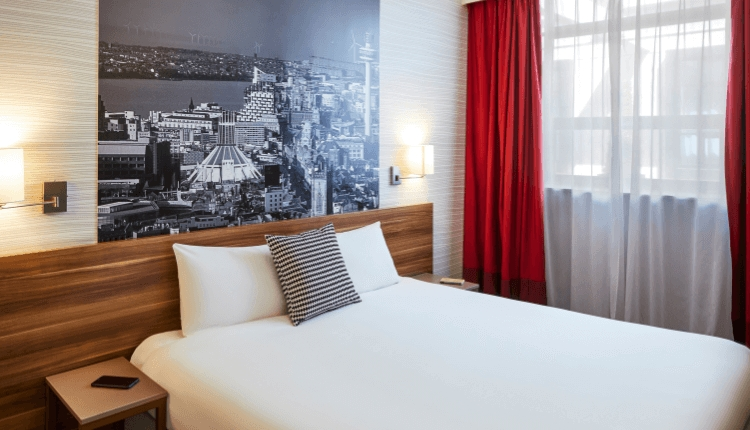 Bed with white sheets in a hotel room with red curtains and a black and white photo of Liverpool on the wall.