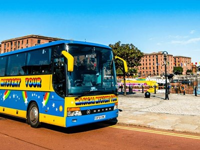 A yellow and blue coach with 'Magical Mystery Tour' in rainbow letters. The coach is parked up on a sunny day by the quayside of Albert Dock.
