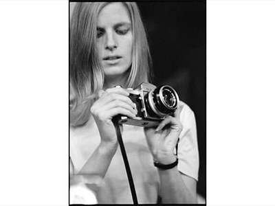 Linda McCartney shown holding a camera in a black and white portrait
