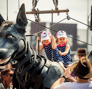 2 youngsters sit on Xolo the giant dog. Just one of 18 ways to enjoy family fun in Liverpool