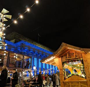 Liverpool Christmas Market, festive huts outside of St George's Hall which is lit up.