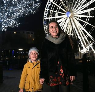A young lady with a young boy outside the Liverpool wheel in Liverpool at night