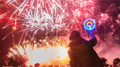 A children sitting on the shoulders of a man watching the fireworks