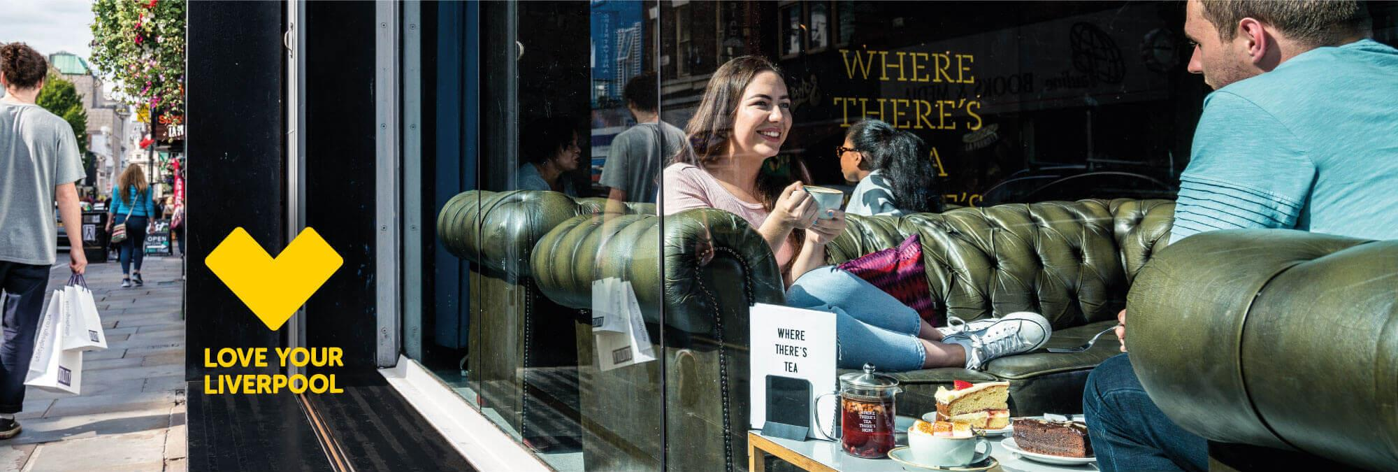A young couple sit in the window of Leaf Cafe on Bold Street