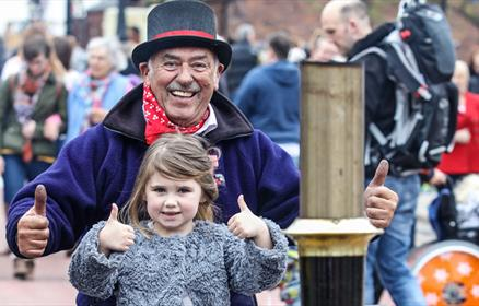 A young girl and older male with thumbs up while sitting on a steam tractor at Steam on the Dock festival