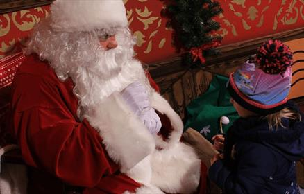 Father Christmas greets a youngster at the Knowsley Safari Grotto